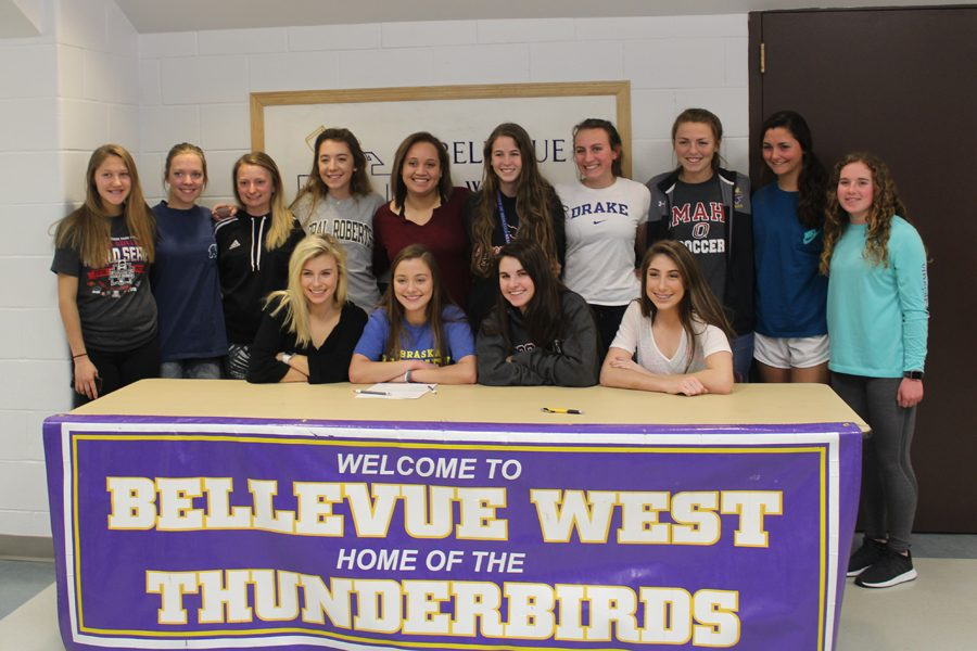 Senior+Megan+Cook+poses+with+the+Bellevue+West+girl%27s+soccer+team+after+signing+with+the+University+of+Nebraska-Kearney.