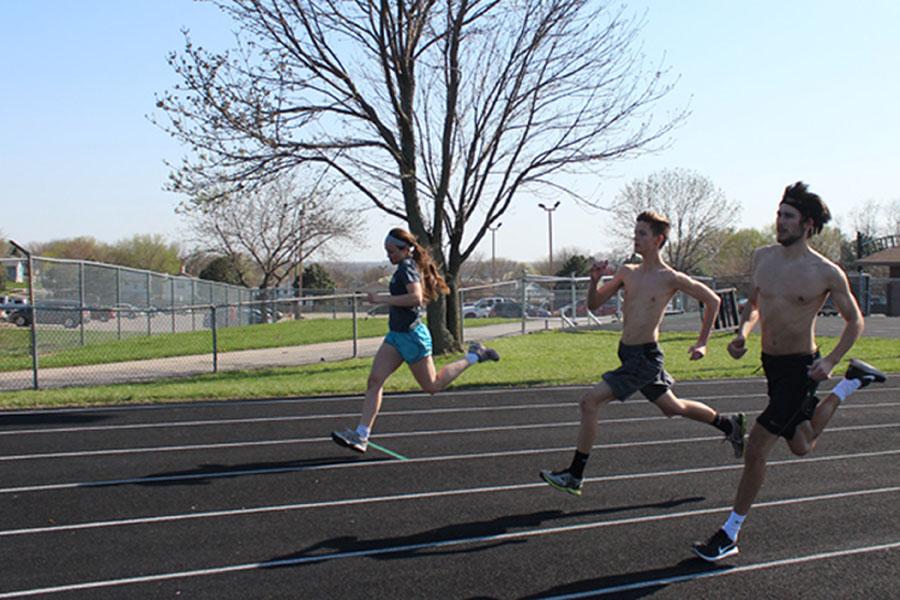Seniors Bryson Williams, Chase Scott and junior Kortney Buresh train for long distance running during practice.