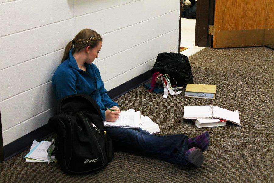 Sophomore+Kristian+Menard+studies+intently+outside+of+her+classroom+.