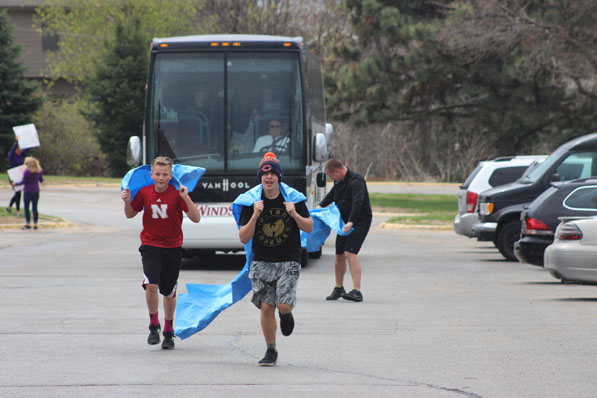 Fans of Bellevue West Winterguard run in front of the bus with two rivers to welcome home the newly crowned World Champion team.