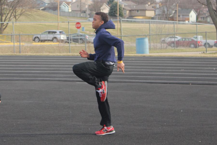 Sophomore Shane Smith participates in warm-ups during a track and field practice on March 9. Smith, who transferred to Bellevue West from Omaha North, participates in long jump, the 4x100 and the 4x400.