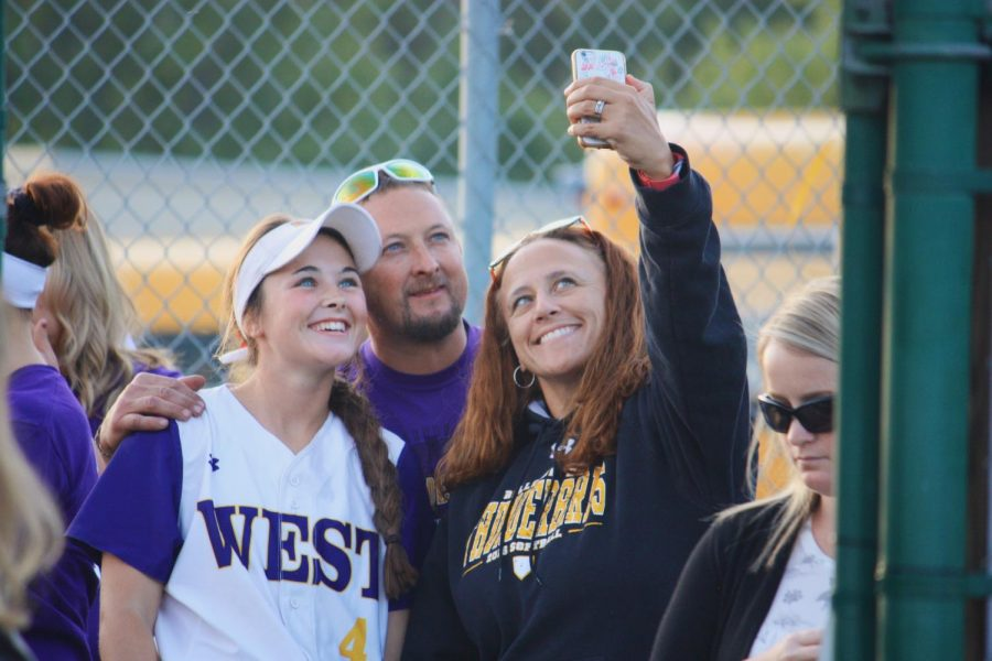 Kortney+Buresh+poses+for+a+picture+with+her+parents+during+softball+senior+night.