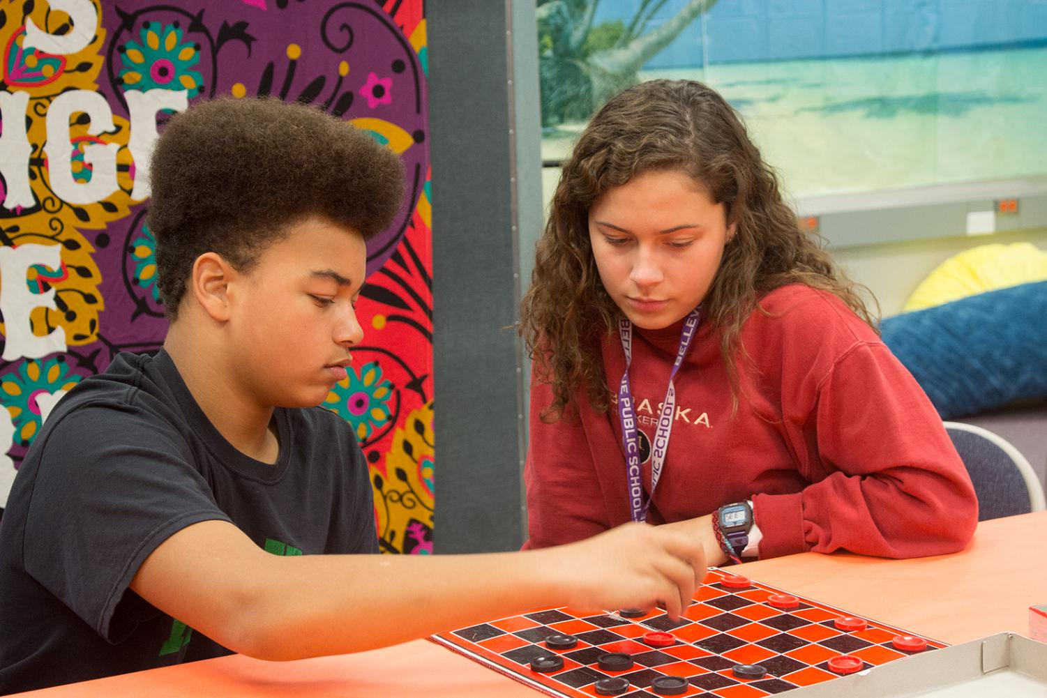 Senior Trinity Torres and eighth grader Jordan Jacobs play a friendly game of chess to get to know each other better.
