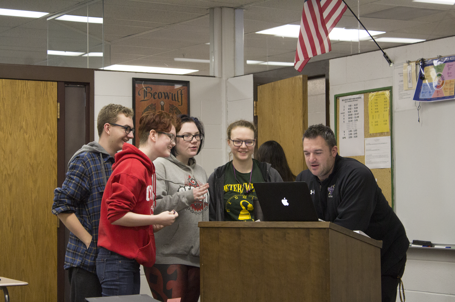 Adam Heuertz consults with students in his first hour English 12 A class about their poetry project.  Next year, English 12 A will no longer be available along with other advanced classes.