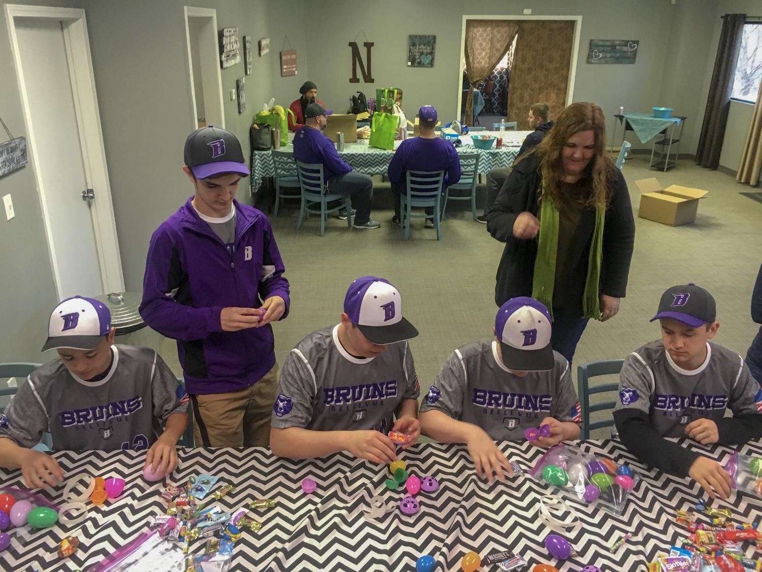 Players on the 14U Bellevue Bruins baseball team fill Easter eggs for their