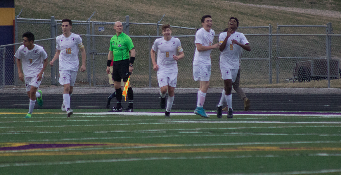 Members of the boys soccer team celebrate a goal against Elkhorn South on April 12, 2017.