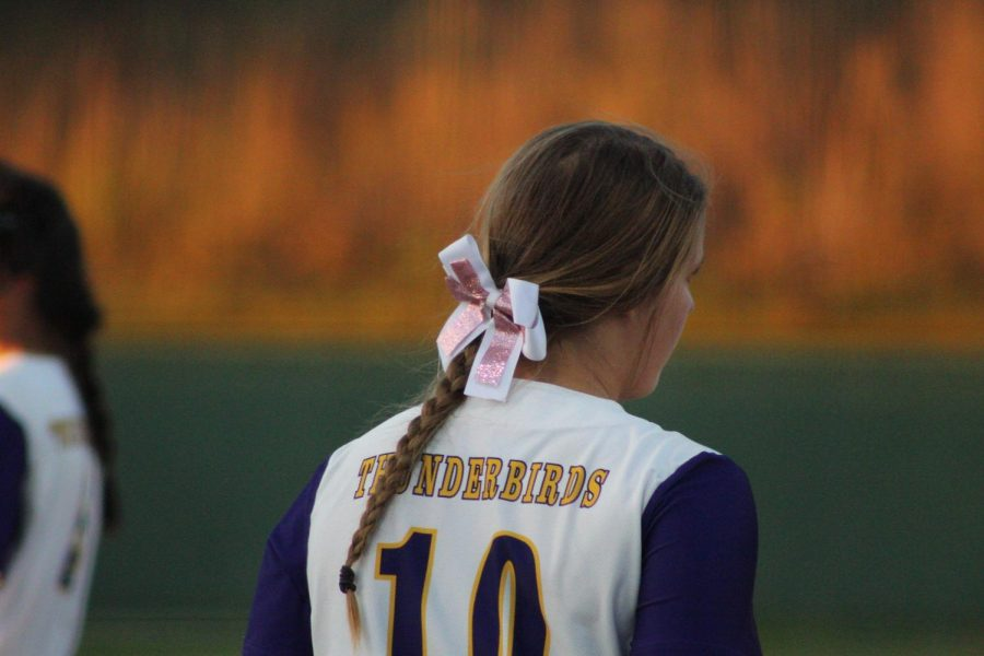 Thunder-bowed. Senior Madison Machacek stands with a pink bow in her hair.