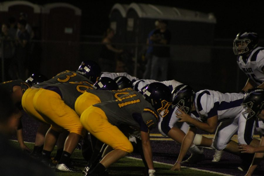 First down. West and East football teams line up for a play.