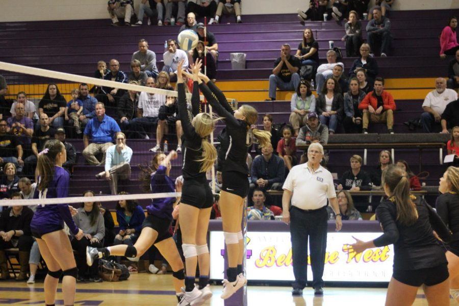 Junior Maddy Madsen and freshman Kealy Kiviniemi go up for a block against Bellevue East on Oct. 16, 2018