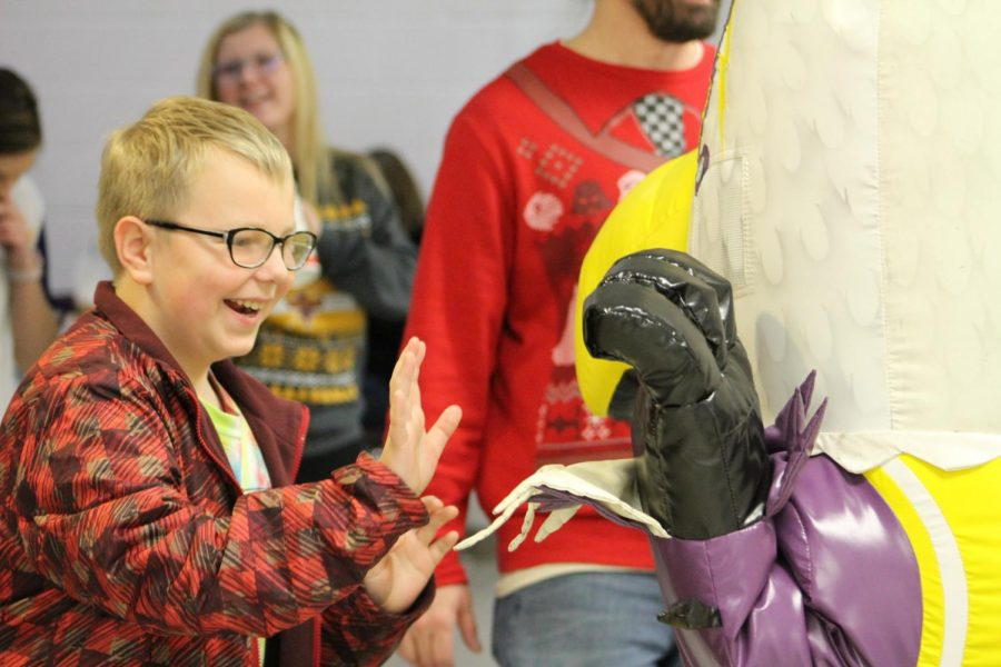 High-five. A child smiles as he high fives the school mascot.