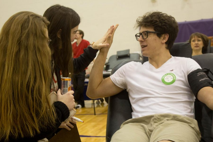Support system. Seniors Morgan Braun and Emily Schiefelbein stand by Jalen Powell before he donates blood.