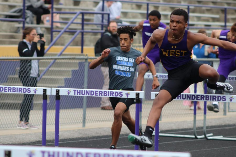 Junior Jerome Houston jumps over a hurdle in the boys 100m hurdle race