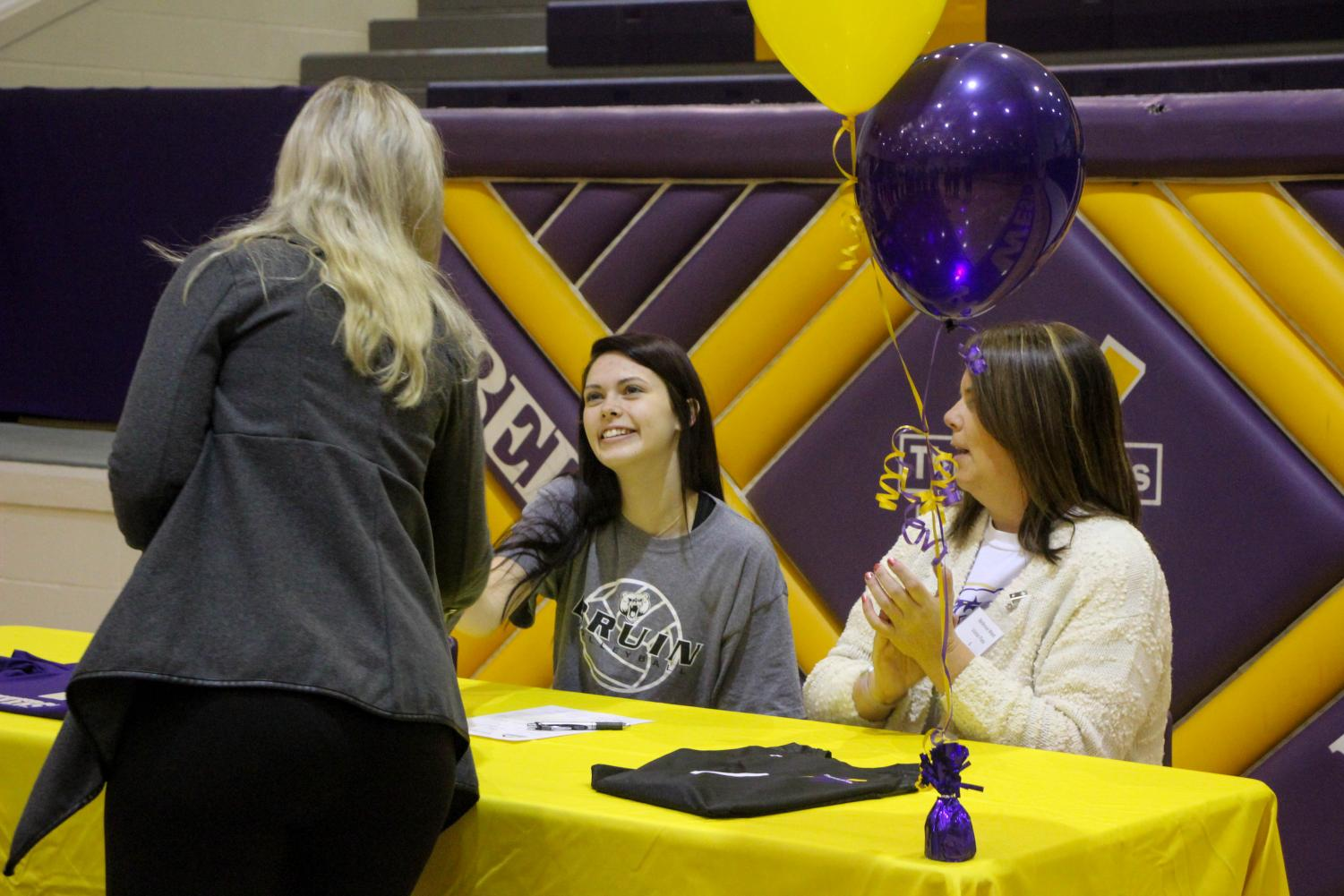 Apel is congratulated on her signing.