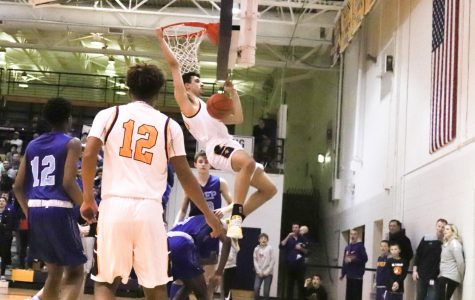 Watch. The players on the court watch as senior John Shanklin makes a slam dunk.