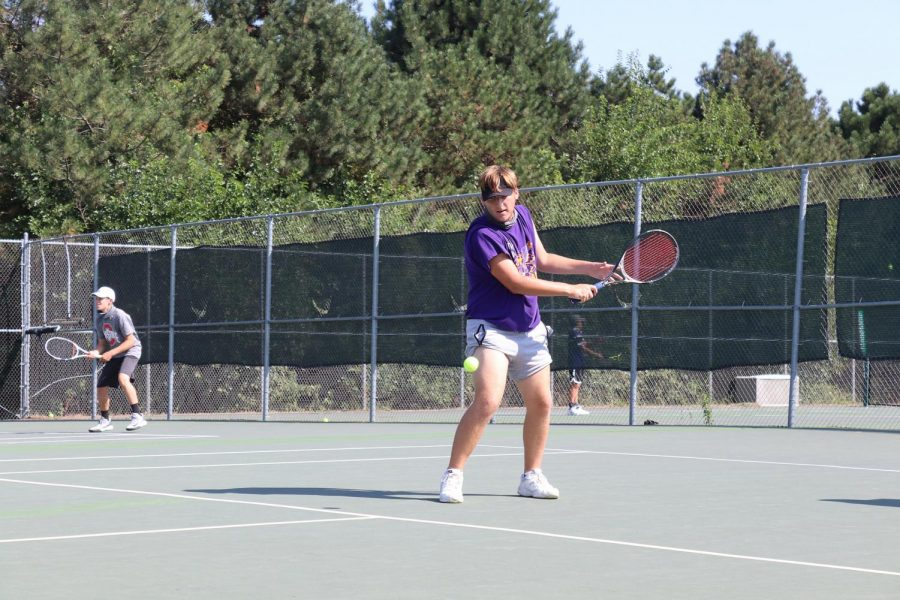 Senior Tyson Forbes loads his racquet to hit a back-handed slice during the varsity team's practice on Aug. 21, 2020.