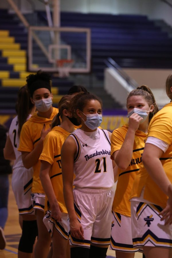 Sophomore Taryn Wharton watches the video board with the team before tip-off.