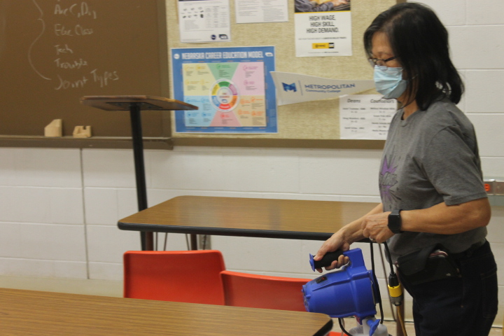 Custodian Nelly Carlson demonstrates how to use the disinfectant fogger machine in a classroom on Dec. 8, 2020.