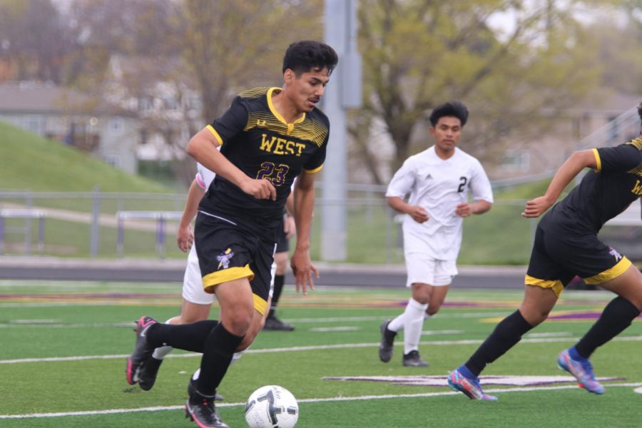 Senior Martin Fuentes watches the ball as he dribbles downfield.