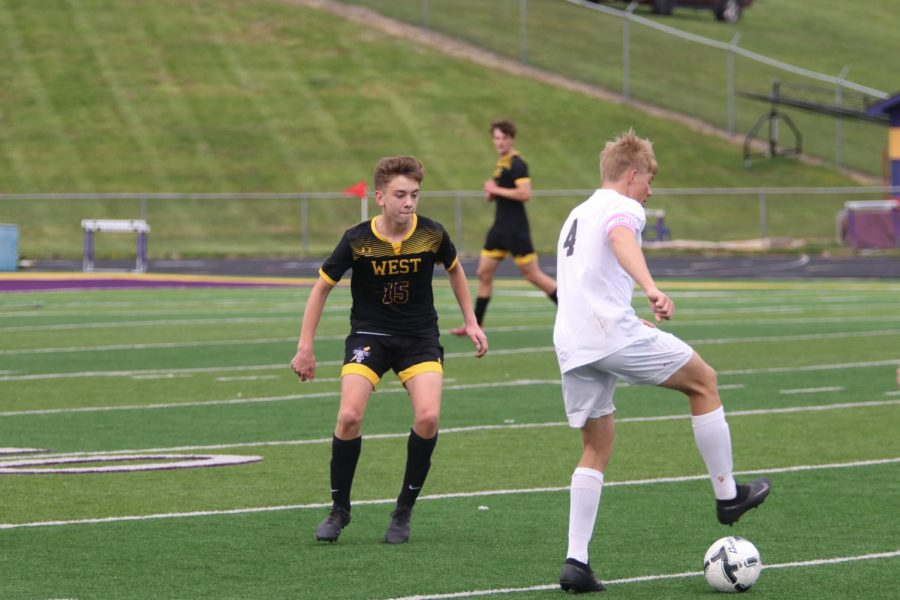 Sophomore Gavan Rachwitz defends against Columbus' Alex Larson.
