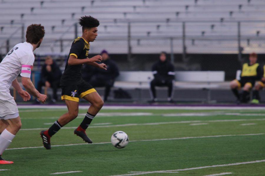 Freshman Octavio Miranda dribbles through open field.