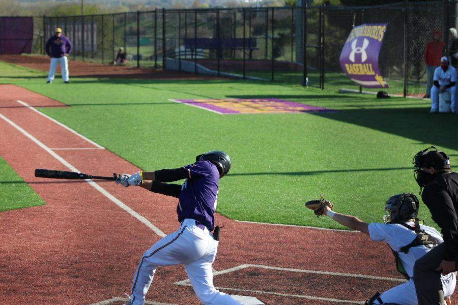 Senior Cam Madsen swings through at bat.