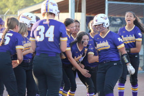 The team celebrates after Senior Emily Mabbitt hits a home run.